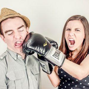 Jeune fille donnant un coup de poing avec un gant de boxe à un garçon