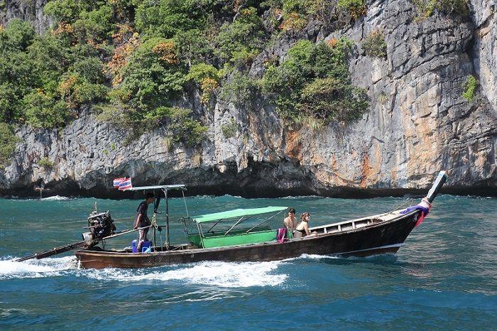 Longtail boat navigant entre les îles avec à bord un couple