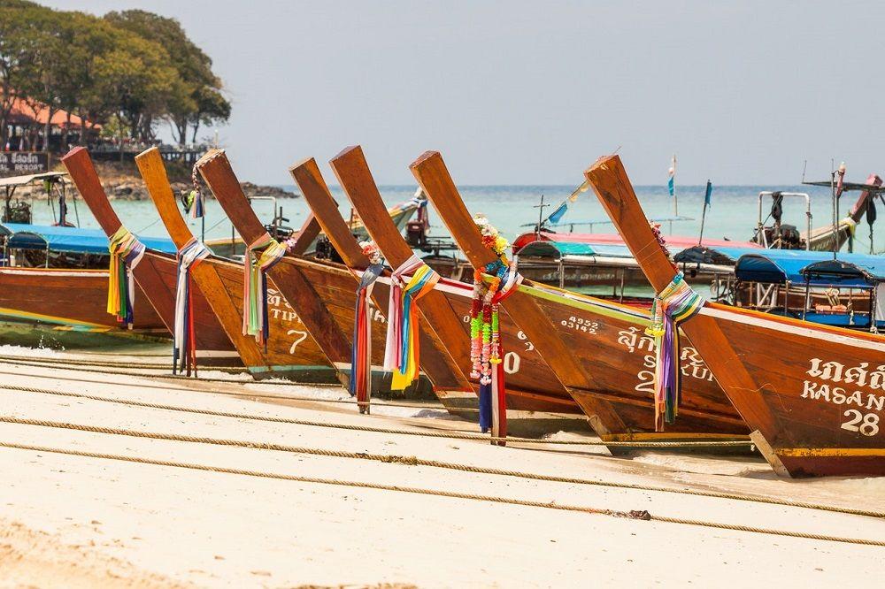 Longtail boats alignés sur une plage, Thaïlande
