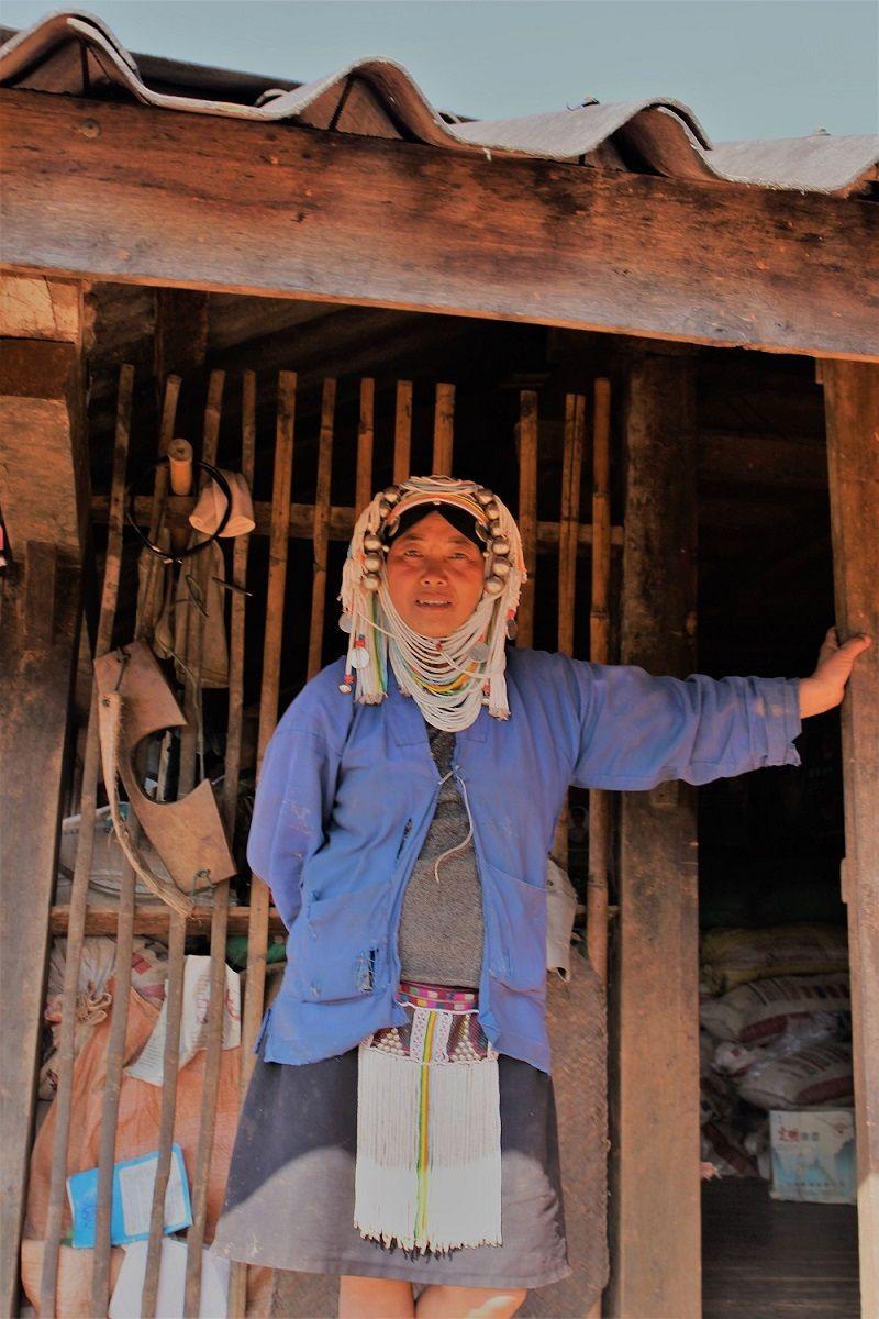 Femme birmane debout devant l'entrée de sa maison en bois