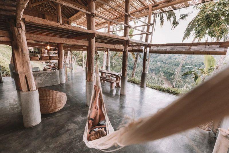 Personne allongée dans un hamac sur la terrasse d'un hôtel en Asie