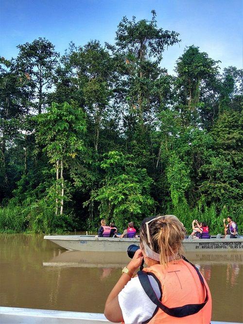touriste assise dans une barque prenant en photo des singes