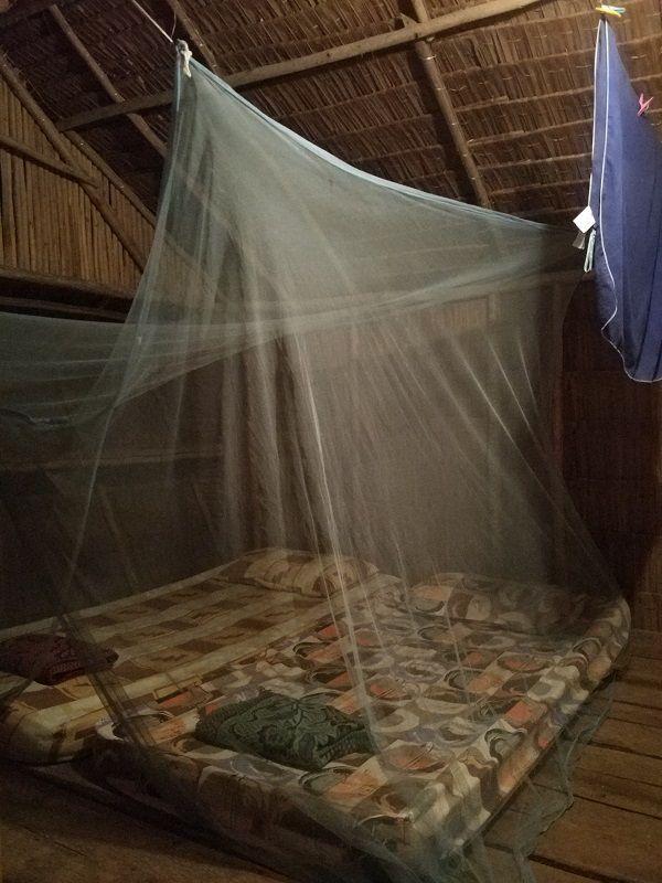 matelas avec moustiquaire dans une cabane en bois