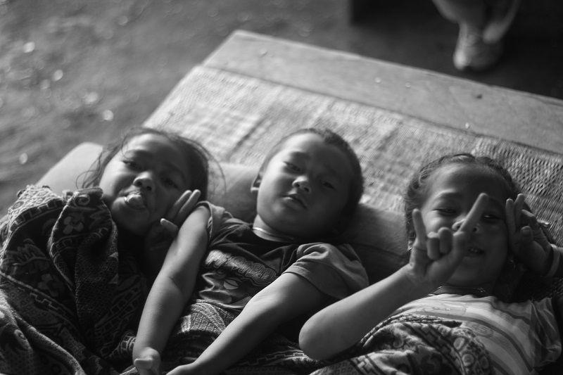 3 enfants asiatiques souriant et faisant des signes de main